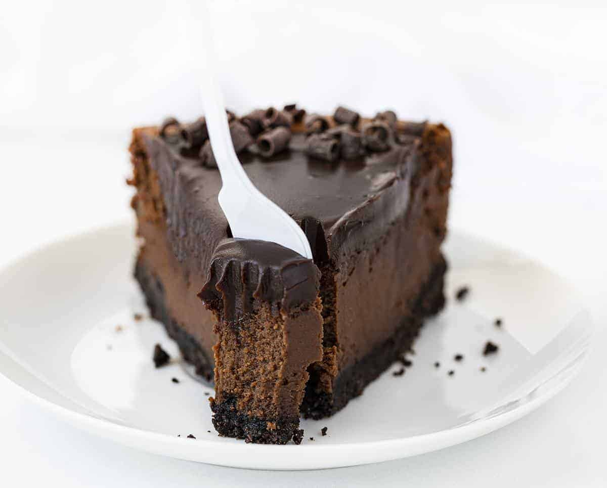 White Fork Removing a Bite from One Slice of Chocolate Cheesecake