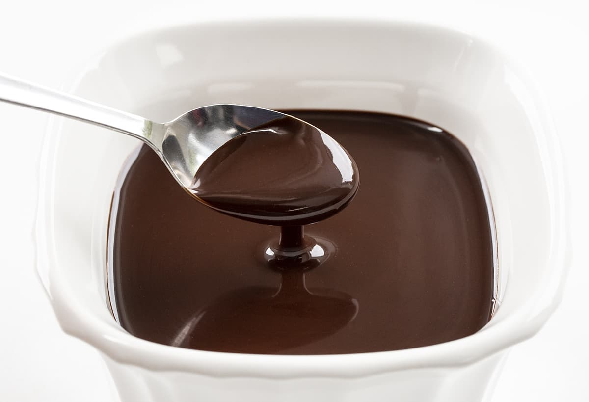 Spoonful of Homemade Chocolate Fudge Sauce that is in a White Square Container