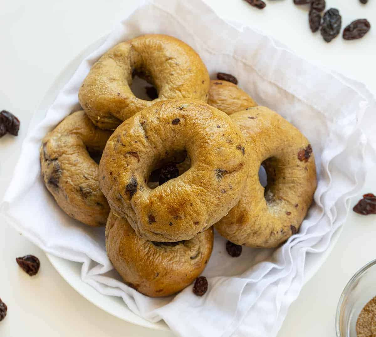 Overhead Image of Cinnamon Raisin Bagels in White Bowl with Raisins around it