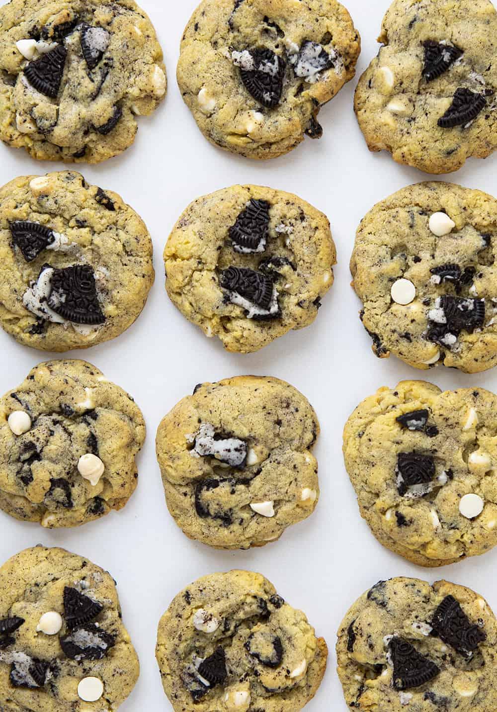 Image aérienne de cookies et de cookies à la crème placés côte à côte sur une surface plane blanche