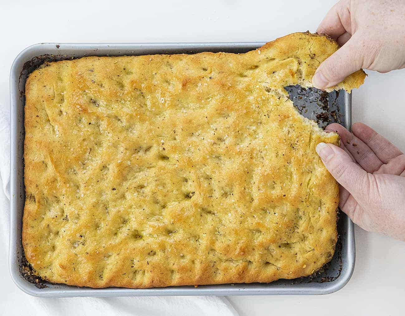 Hands Tearing off a Piece of Focaccia Bread