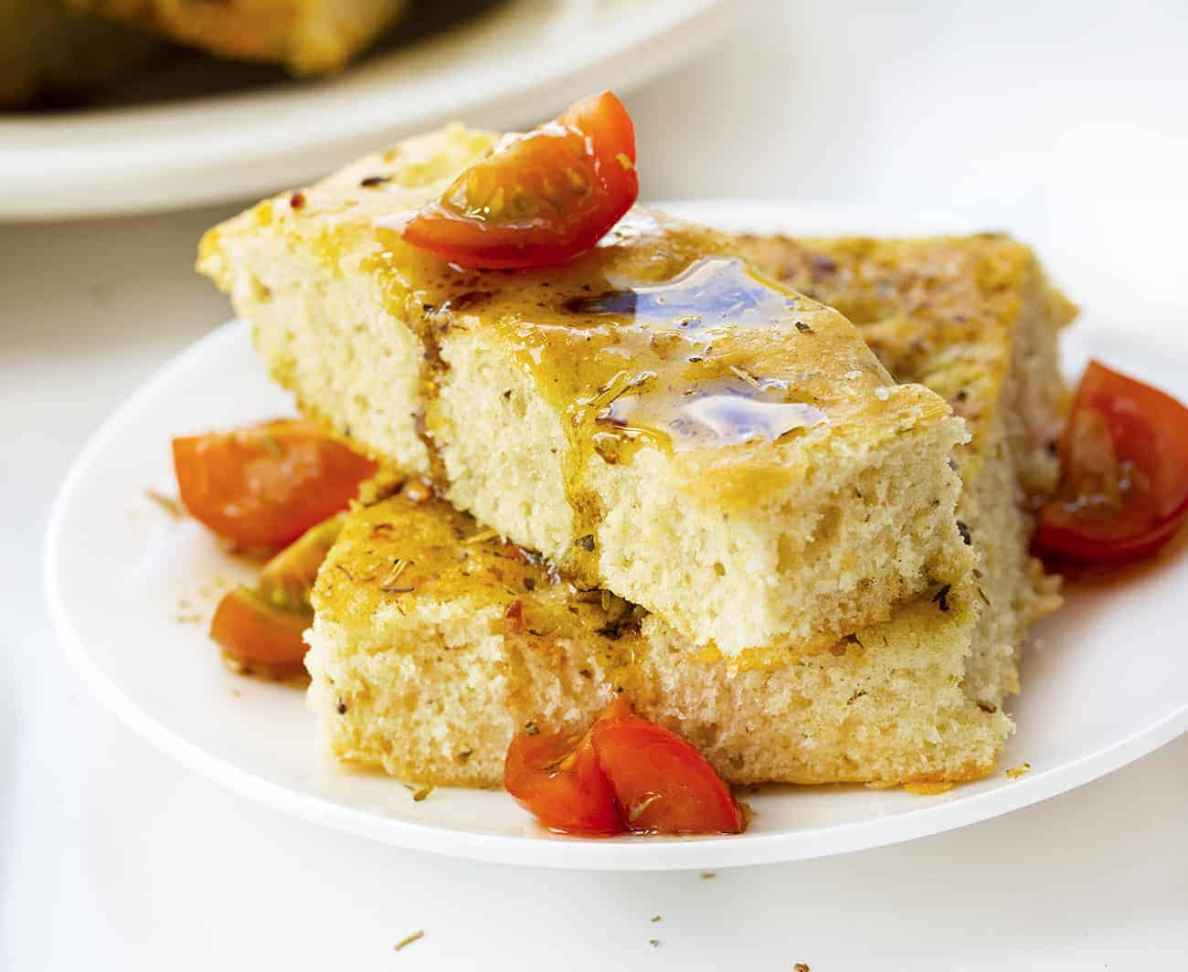 Focaccia Bread that has been Drizzled with Oil and Balsamic Vinegar on a White Plate with Tomato