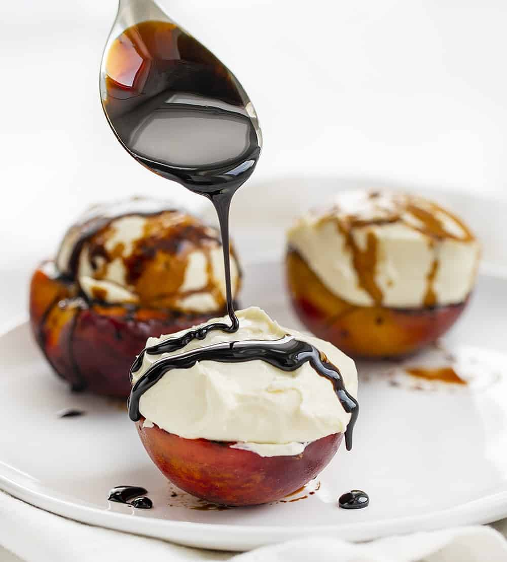 Drizzling Balsamic Glaze over Grilled Peaches with Vanilla Chai Cream