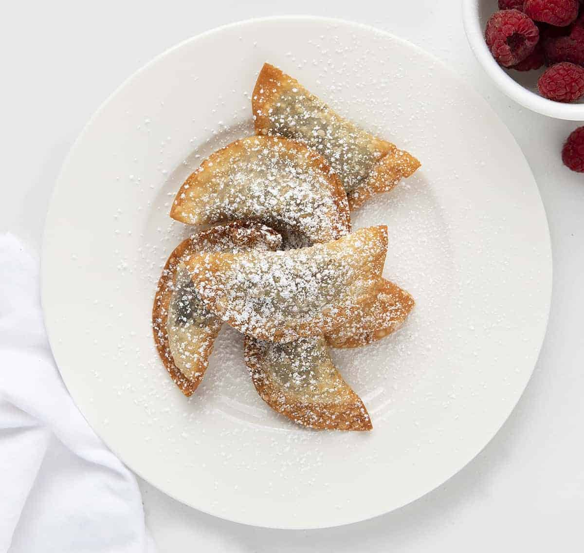 Deep Fried Oreo Wontons on a White Plate with Raspberries in Back
