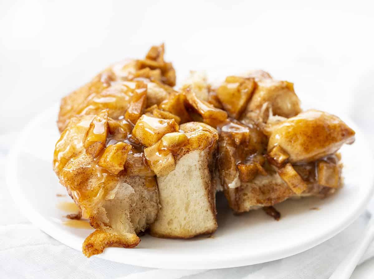 Morceaux de pain de beignet aux pommes sur une plaque blanche avec une fourchette blanche