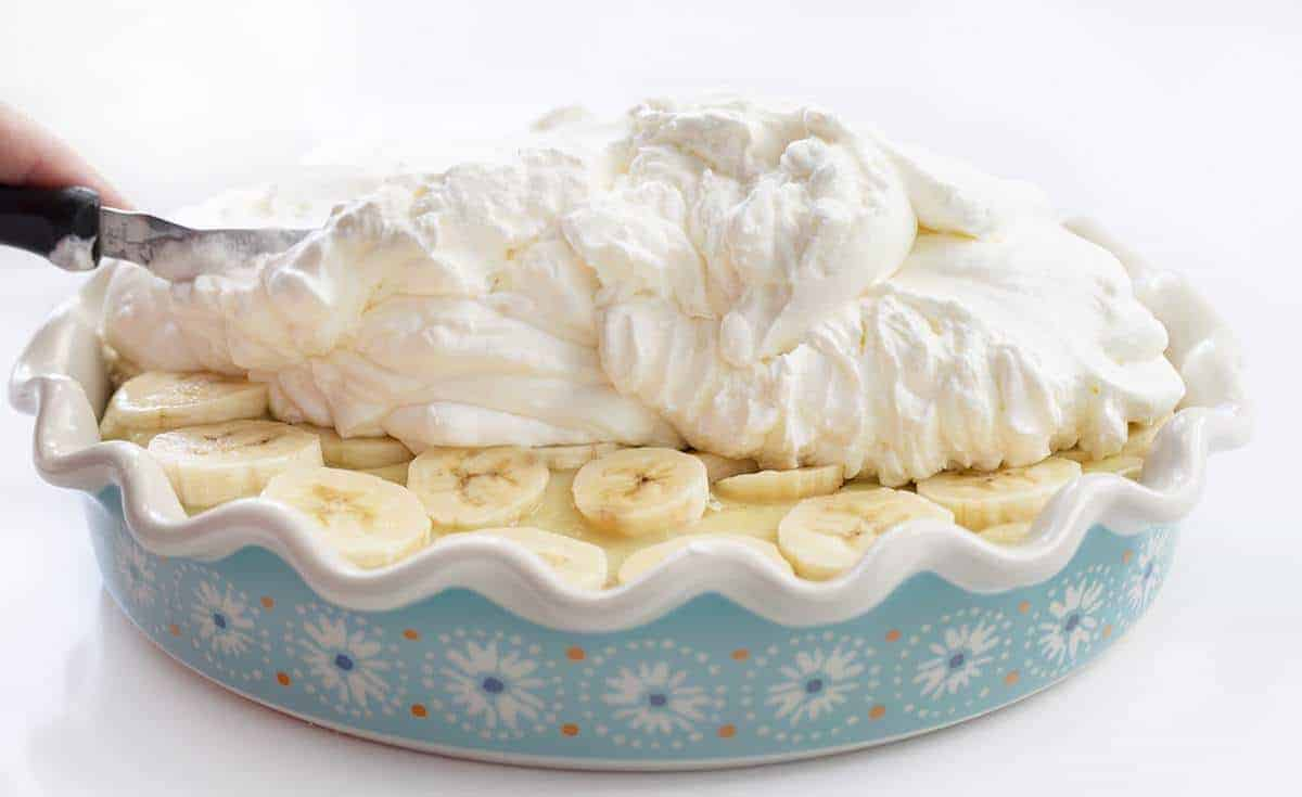 Spreading Fresh Made Whipped Cream over Banana Cream Pie