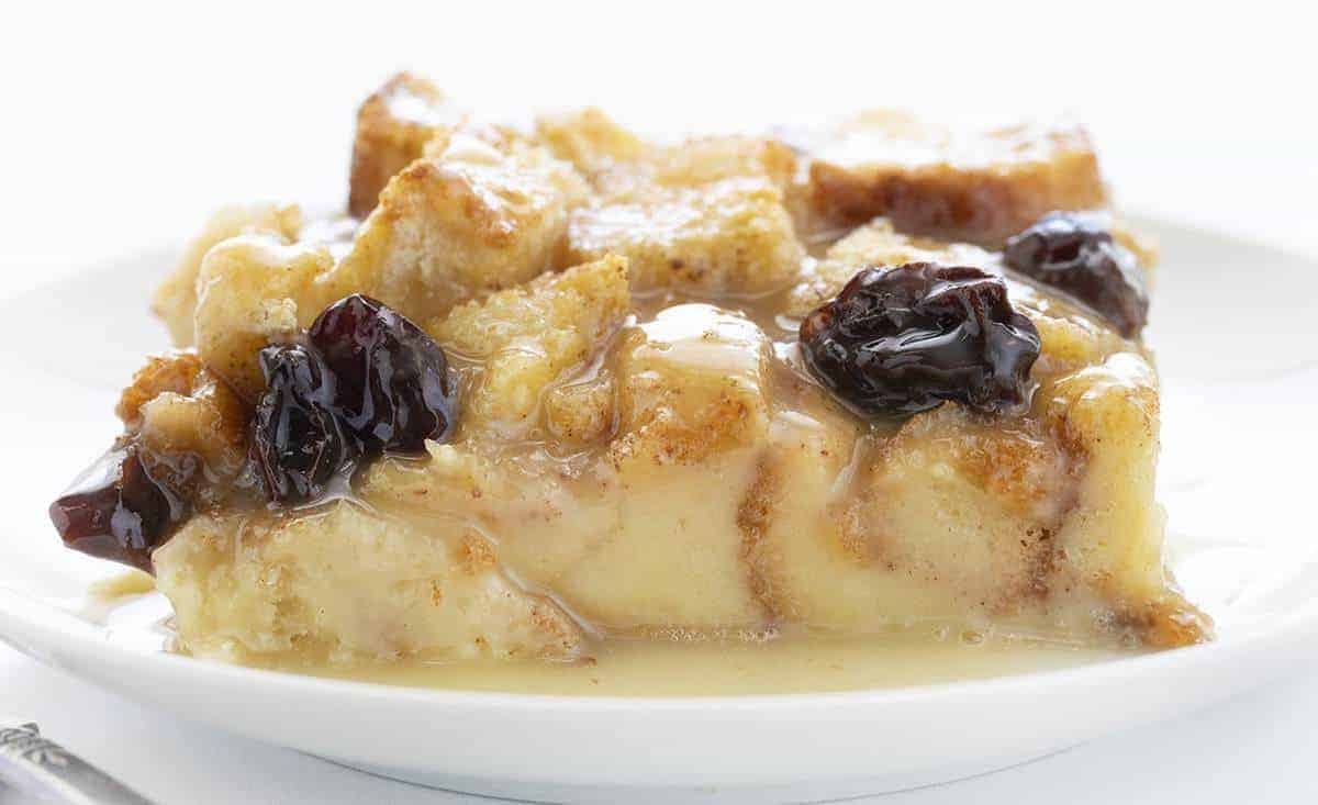 Very Close Piece of Old Fashioned Bread Pudding with Raisins on White Plate