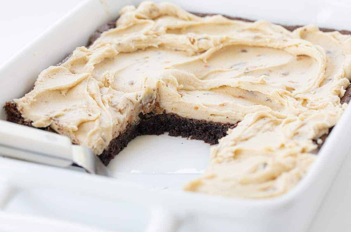 Butterfinger Brownies in a White Pan with Pieces Missing