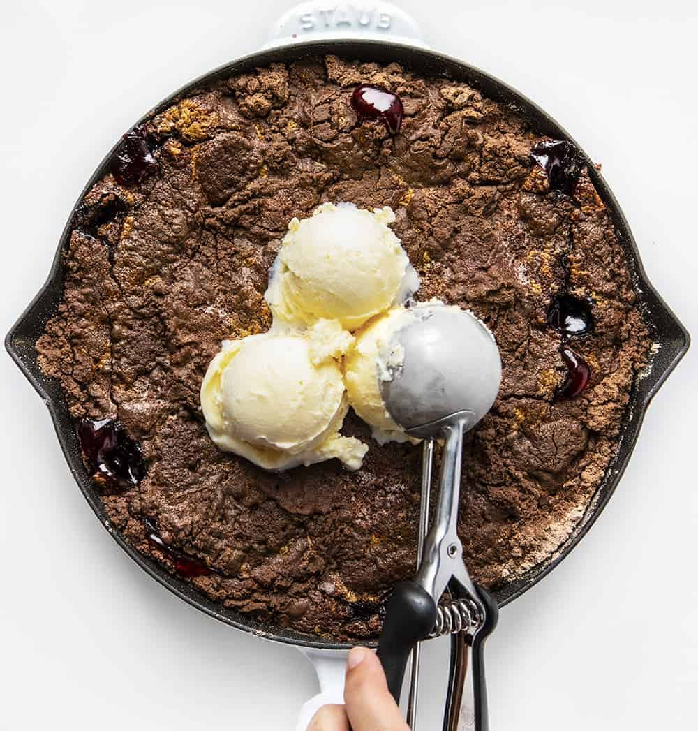 Adding Ice Cream to Baked Chocolate Cherry Dump Cake Recipe in White Skillet