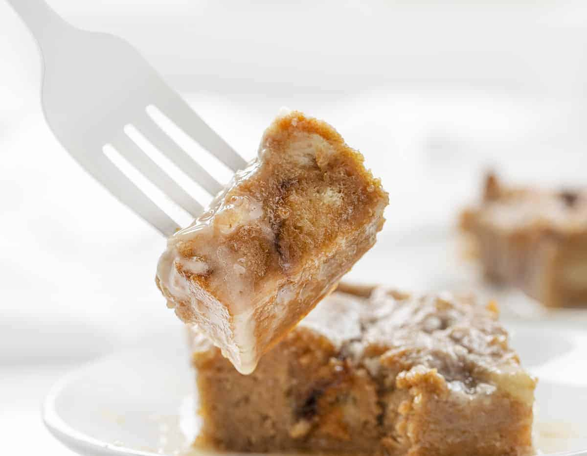 White Fork holding Bite of Chocolate Caramel Bread Pudding Recipe and Plate Behind It