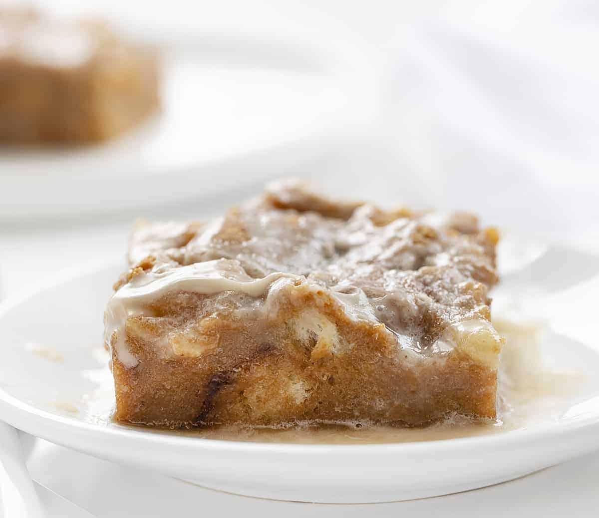 Une tranche de pouding au pain au chocolat et au caramel sur une plaque blanche