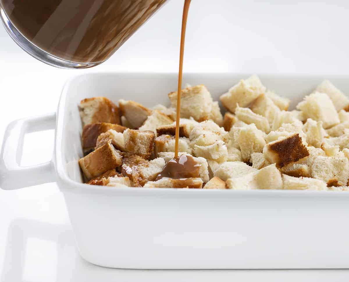 Verser le glaçage aux œufs en chocolat sur le pain séché pour la recette de pudding au pain au caramel au chocolat