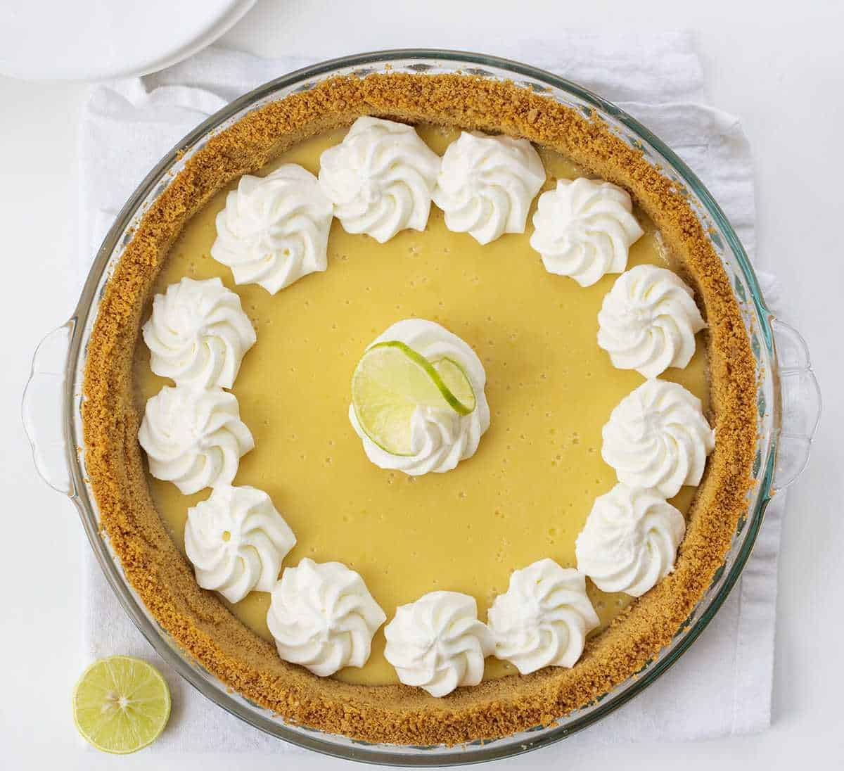 Overhead View of Key Lime Pie with Whipped Cream Dollops and a sliced key lime next to it
