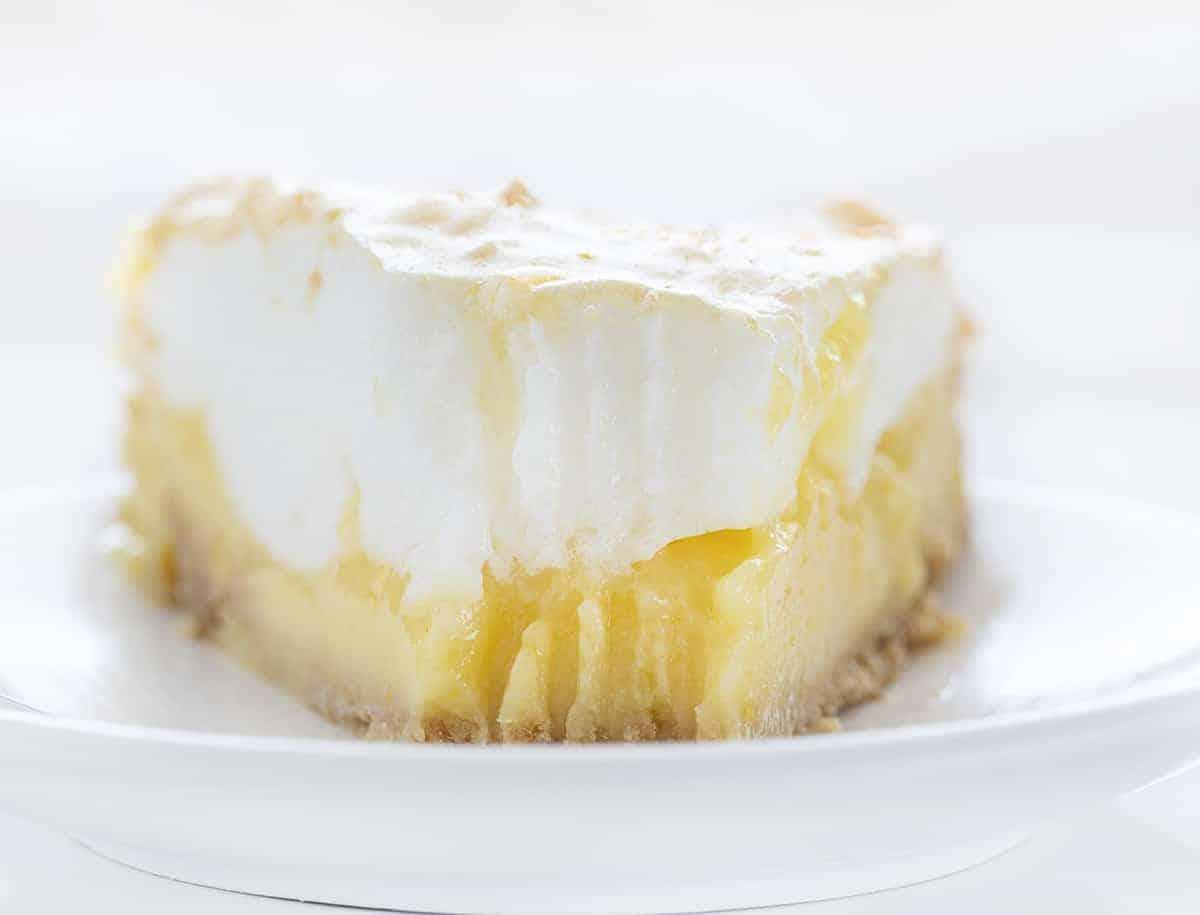 Fatia de torta de limão e merengue com uma mordida removida pelo garfo