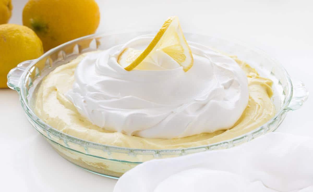 One Lemonade Pie in Glass Pie Pan with Lemons Behind It