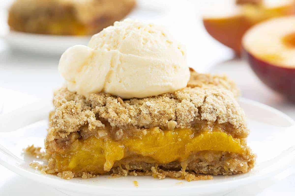 One Piece of Peach Crisp on White Plate with Ice Cream on Top