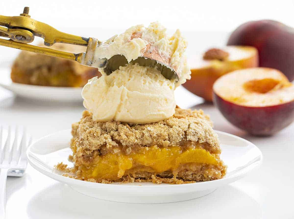 Adding Ice Cream to a Piece of Peach Crisp on a White Plate