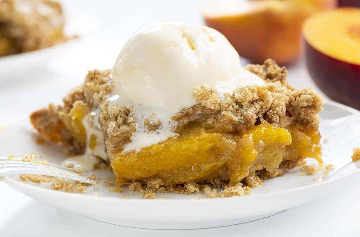 Piece of Peach Crisp with Bite Missing and Fork Resting on Plate