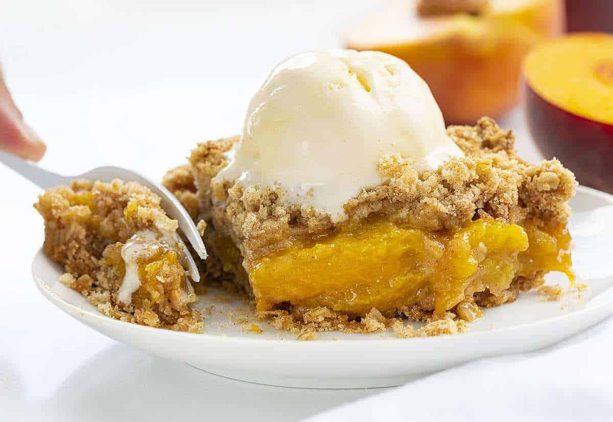 Piece of Peach Crisp on a White Plate with Fork Taking a Bite
