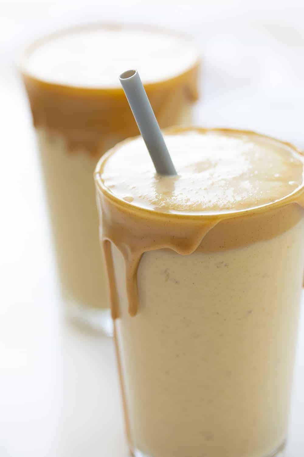 Two Glasses of Peanut Butter Banana Smoothies with Grey Plastic Straw