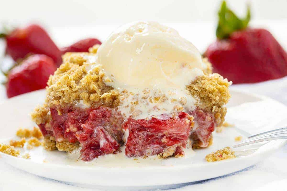 One PIece of Strawberry Crisp on a White Plate with Ice Cream
