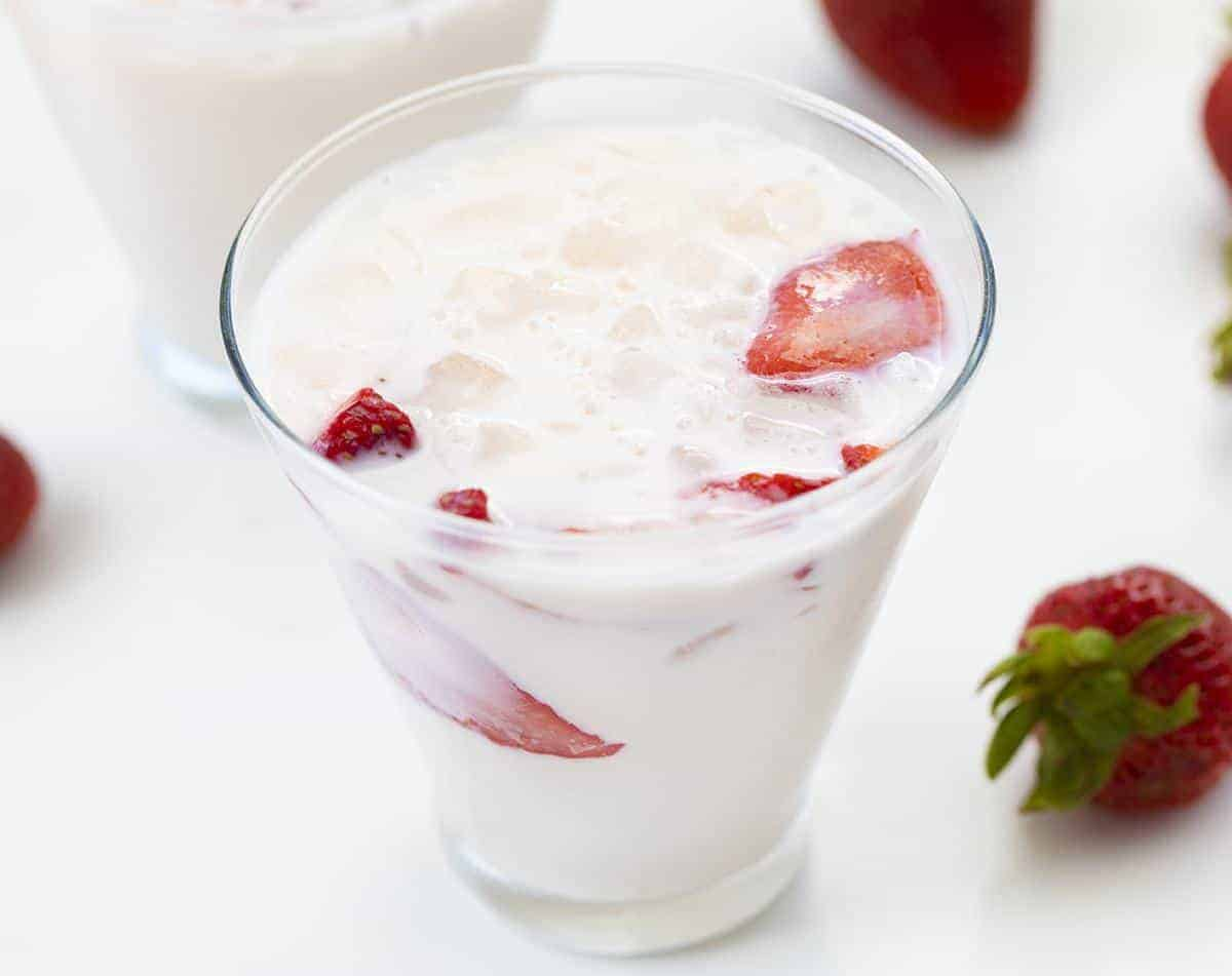 Glass of Strawberries and Cream Milk with Strawberries around it