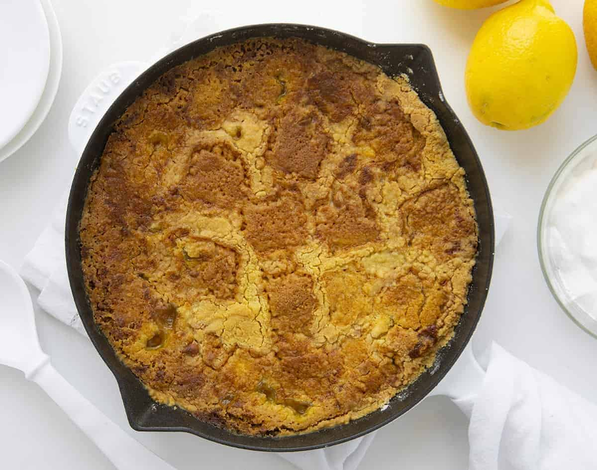 Overhead Image of Lemon Cream Cheese Dump Cake in White Skillet with Lemons and Utensils Around It