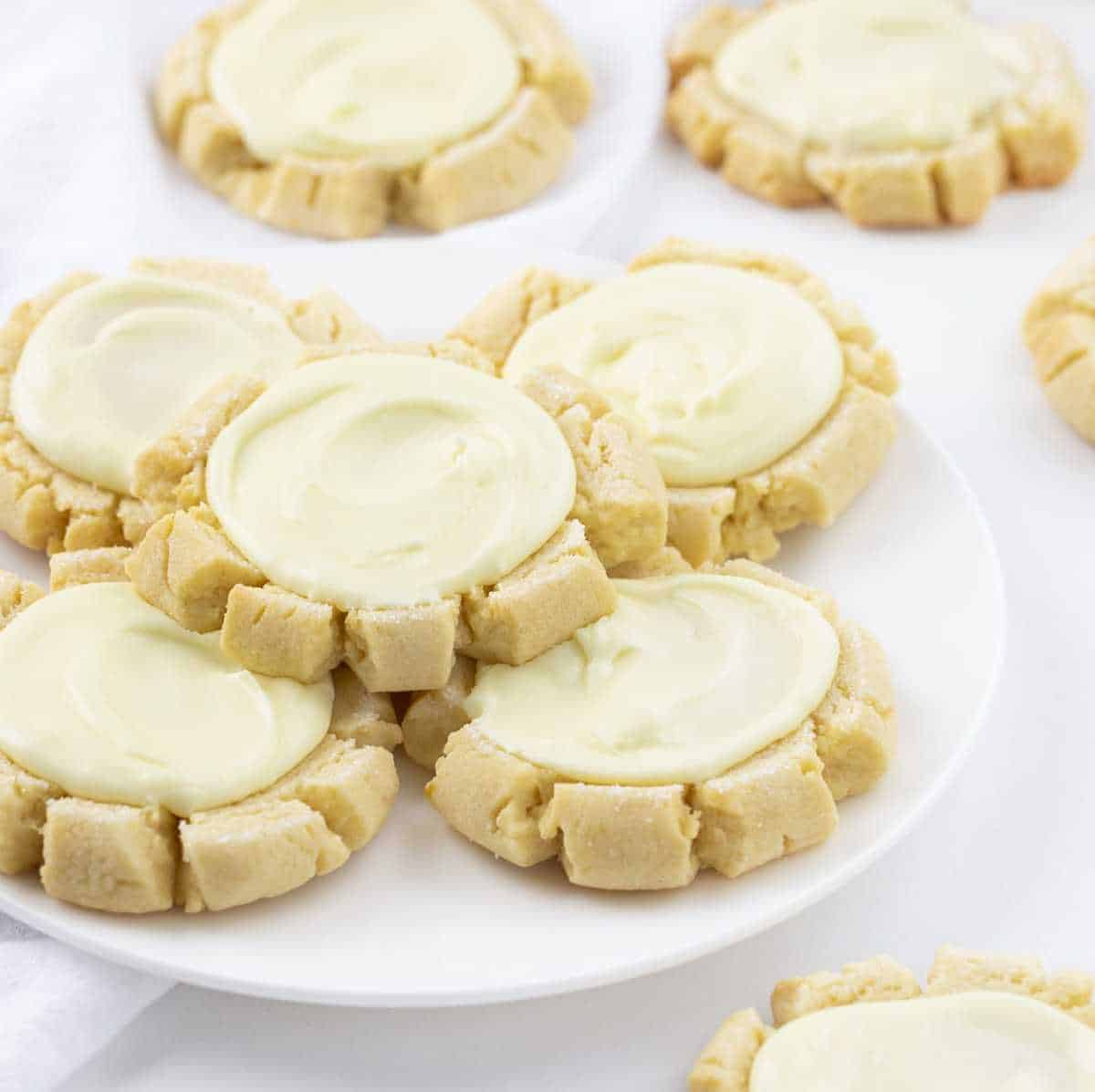 Lemon Sugar Cookies with Lemon Frosting on a White Plate with Cookies around