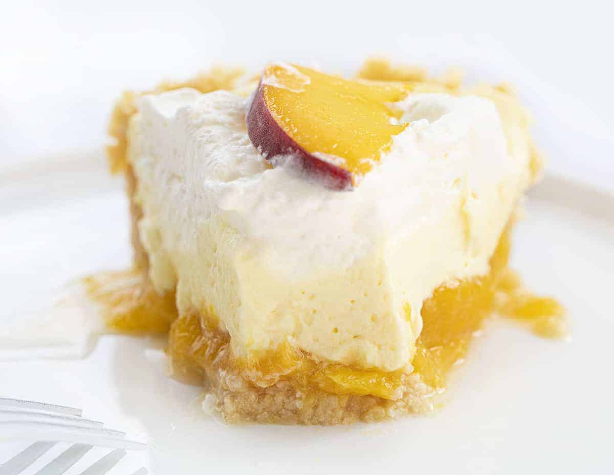 Piece of Peaches and Cream Pie on White Plate with Bite Missing
