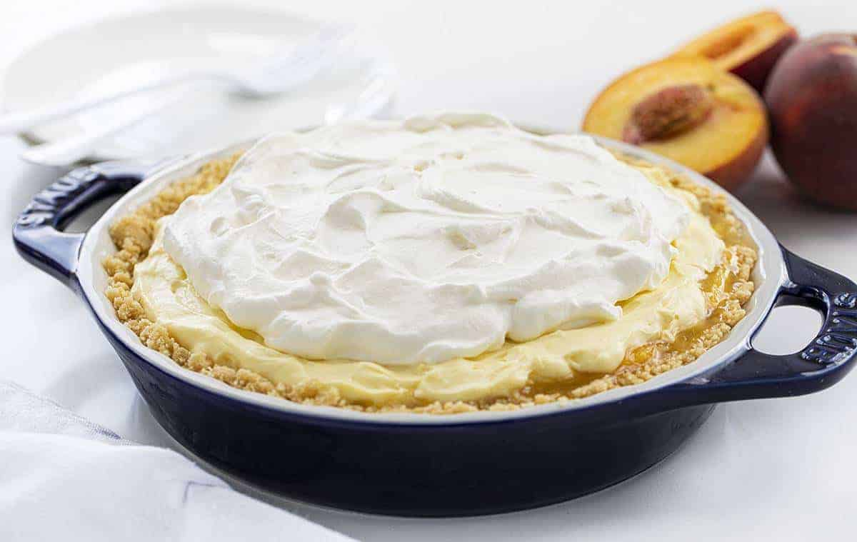 Peaches and Cream Pie in a Blue Pie Dish with Peaches in Back
