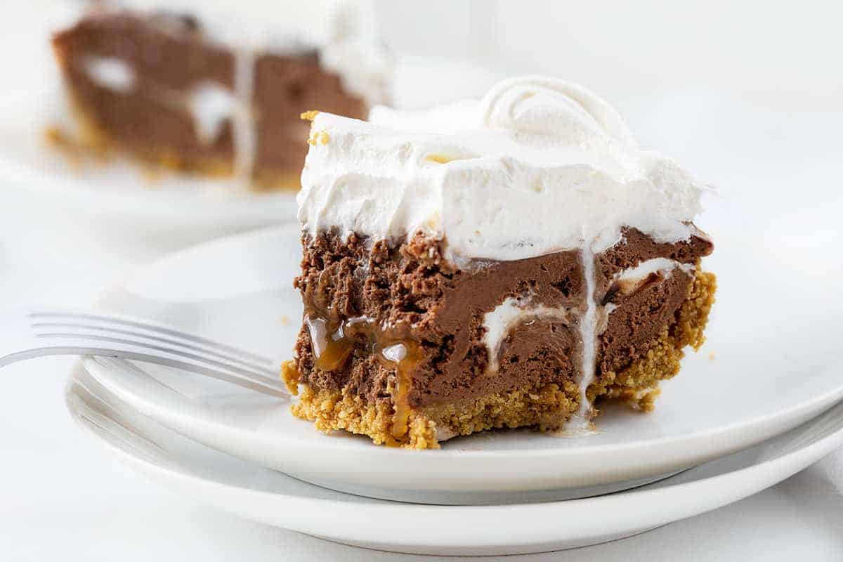 Chocolate Caramel Marshmallow Cheesecake Pie with One Bite Removed Showing Caramel and Marshmallow Inside