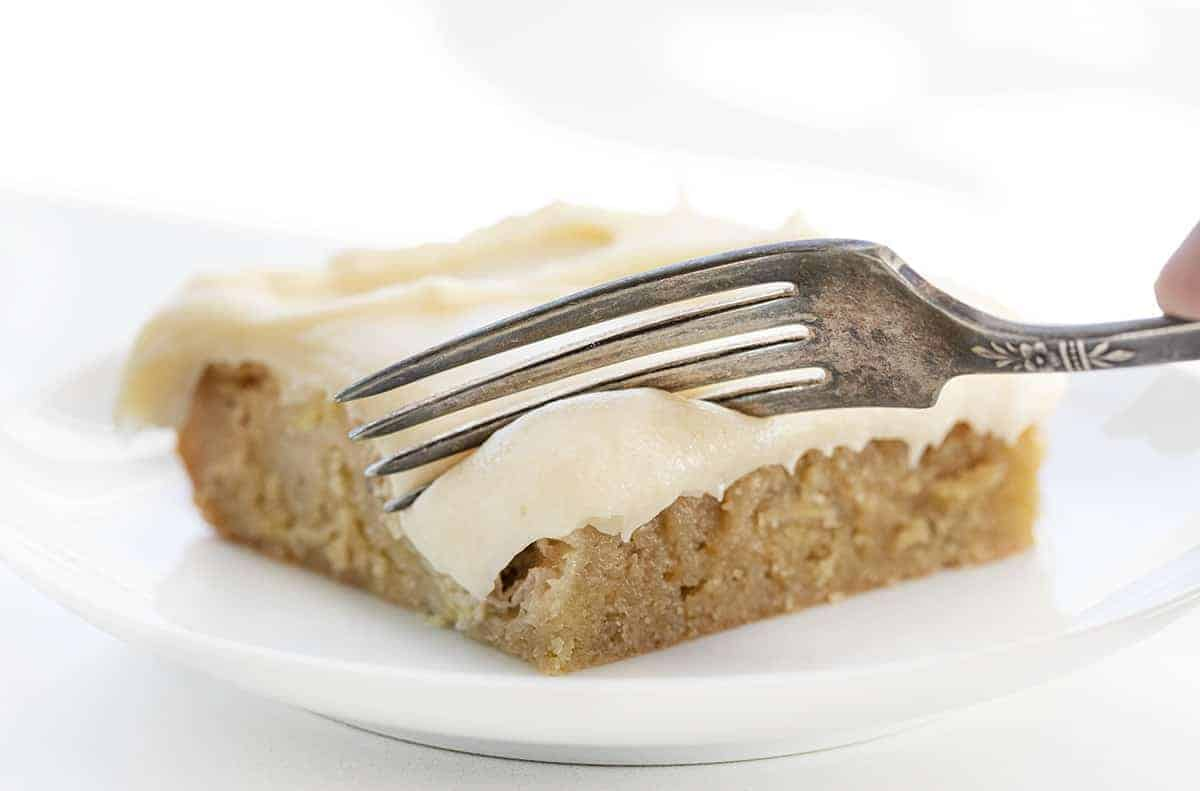 Fork Taking a Bite out of Ooey Gooey Banana Bars with Salted Caramel Frosting