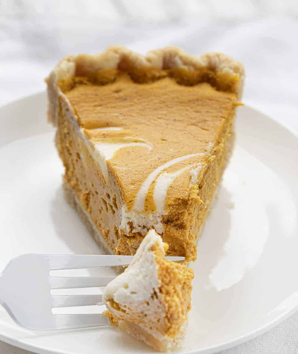 One Piece of Pumpkin Cream Cheese Pie on Plate with Fork Taking Bite