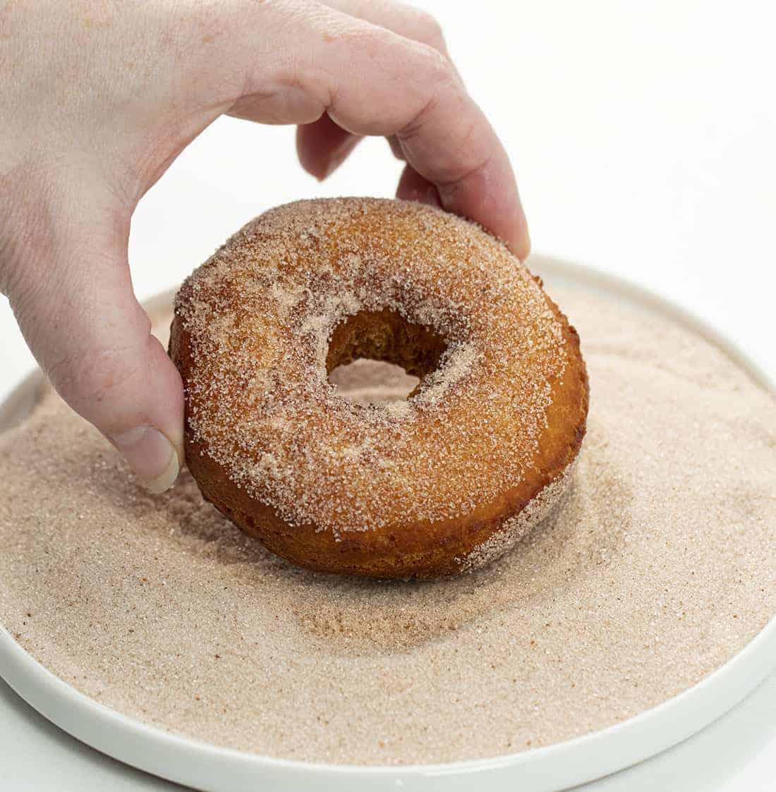 Dipping Fried Apple Cider Donut in Cinnamon Sugar
