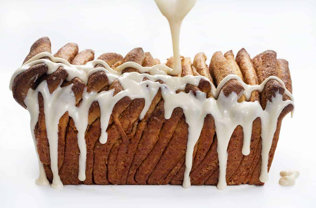 Poring Frosting Over Cinnamon Roll Pull-Apart Bread