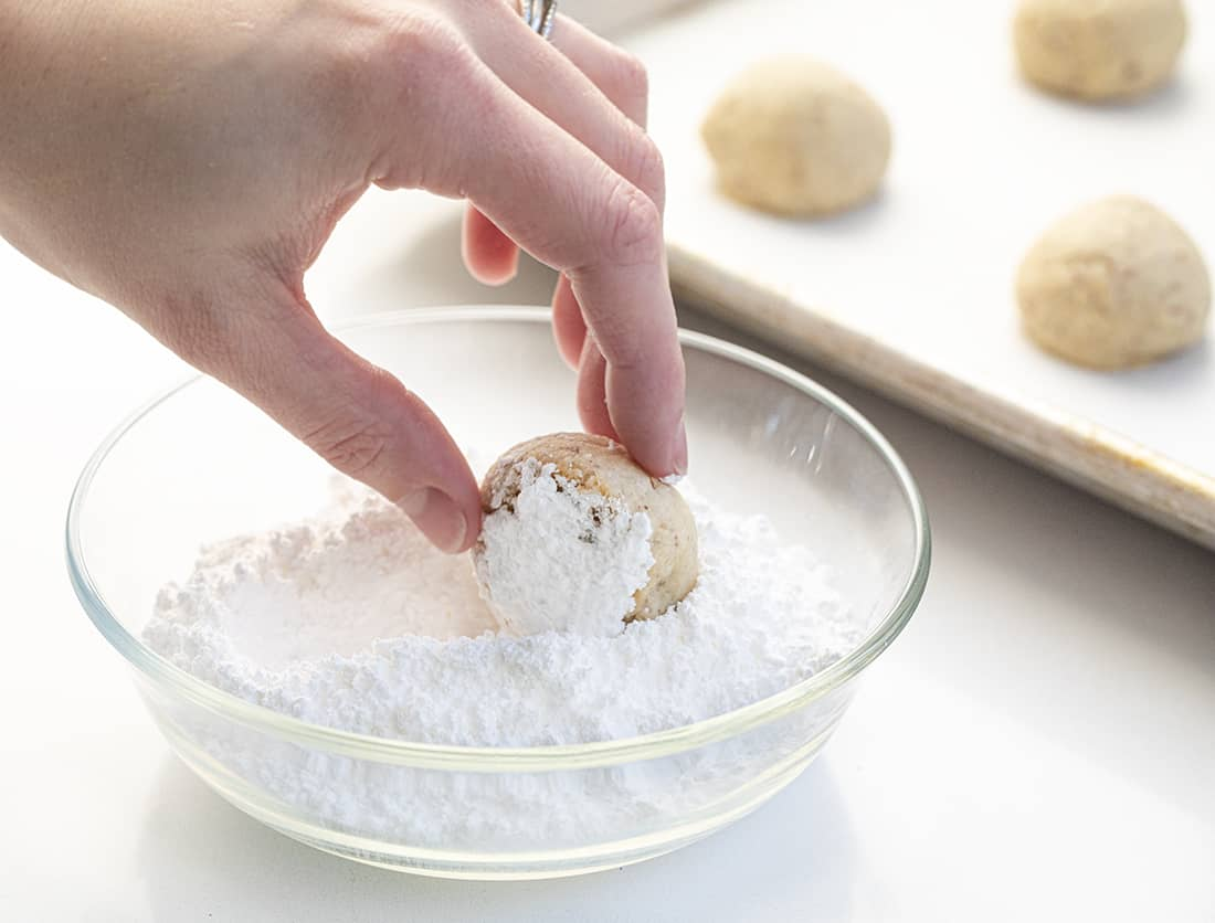 Snowball Cookies - Mexican Wedding Cookies Recipe Being Rolled in Confectioners Sugar