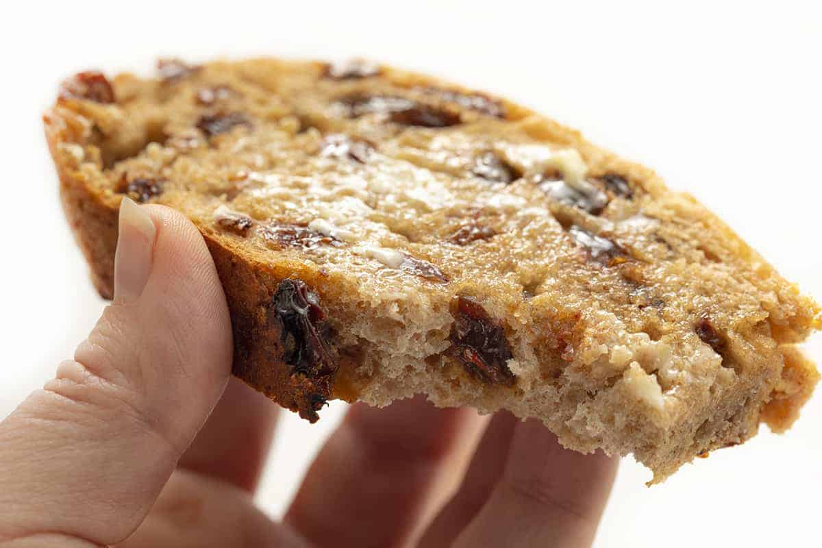 Hand Holding Piece of Cinnamon Raisin Bread
