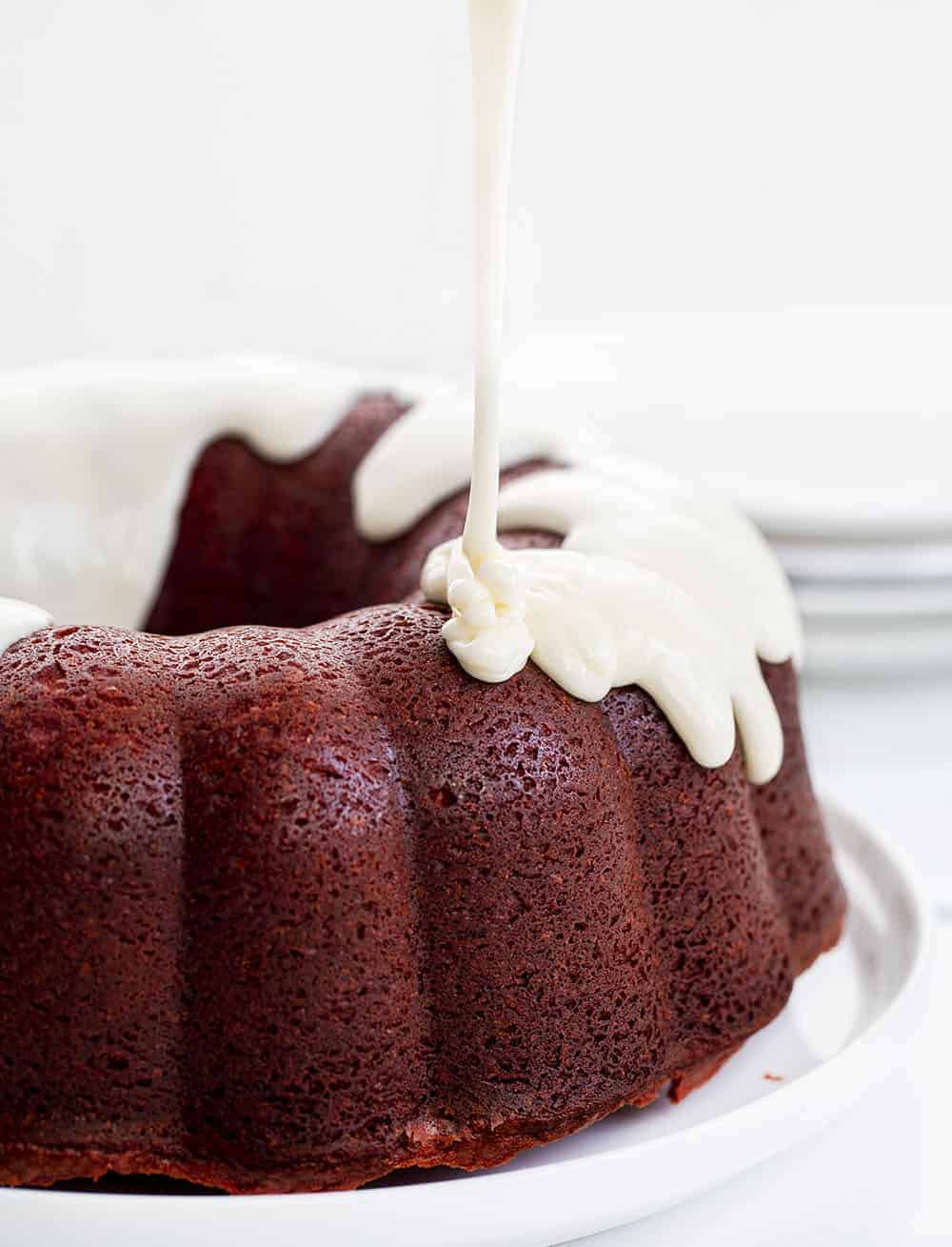 Pouring Cream Cheese Frosting over Red Velvet Pound Cake