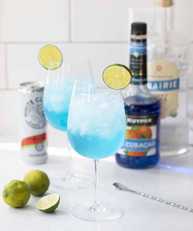 Two Drunken Mermaid Cocktails with Ingredients Behind