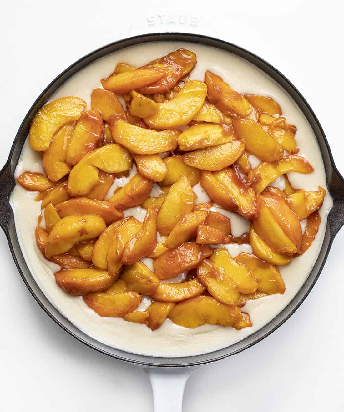 Adding Peaches to Batter in White Skillet