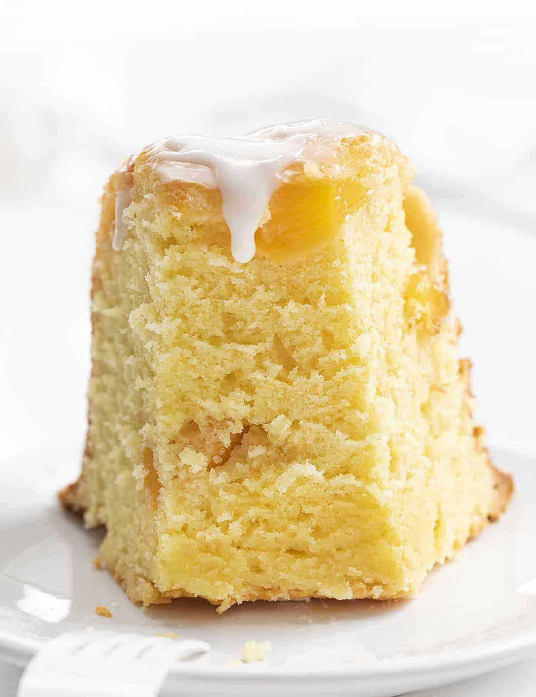 Slice of Peach Pound Cake with Vanilla Glaze on White Plate